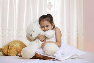 Portrait of girl hugging teddy bear