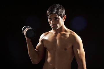 Young man exercising with dumbbell isolated over black background