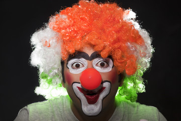 Surprised male clown over black background