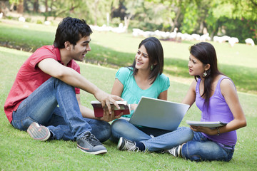 Group of three friends sitting in lawn