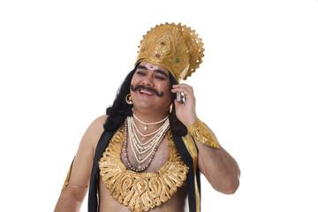 Man dressed as Raavan talking on a mobile phone