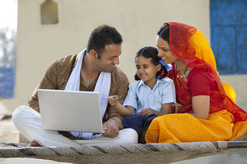 Happy rural family using laptop