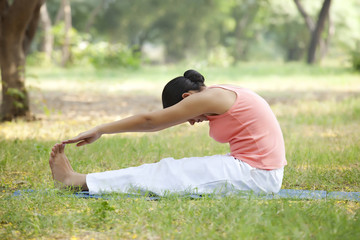 Woman doing stretching exercise at lawn