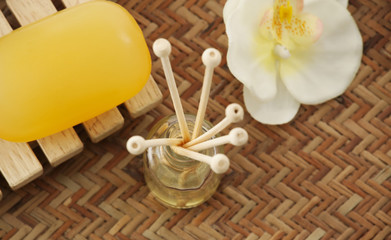 Close-up of soap , reed diffuser and orchid