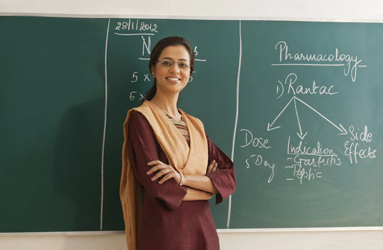 Portrait of young female teacher in traditional clothing standing with arms crossed against chalkboard