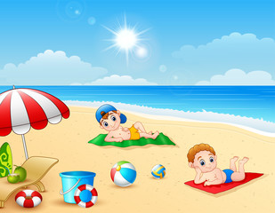 Two boy sunbathing on the beach mat