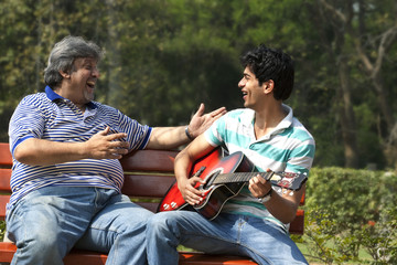 Father listening to his son play the guitar
