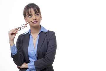 Beautiful young female executive holding glasses while looking away