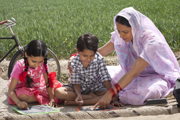 Mother helping daughter and son with their homework