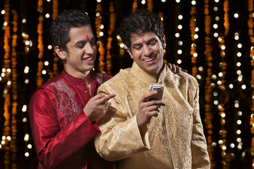 Men smiling at sms on mobile phone