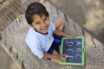 Portrait of a little school boy writing on slate