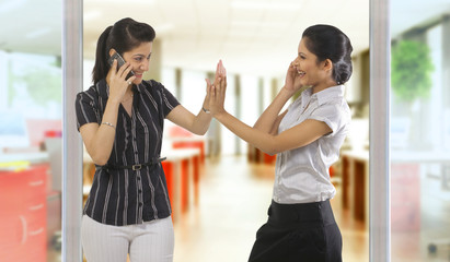 Businesswomen with mobile phones giving a high five