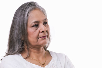 Mature woman lost in thoughts over white background