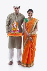 Portrait of a Maharashtrian couple with a Ganesh idol