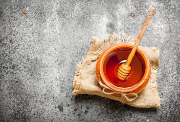 Wall Mural - Fresh honey in a clay pot with a wooden spoon.