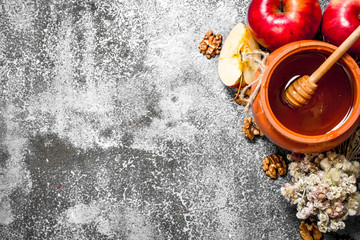 Wall Mural - Honey background. Fragrant honey in a pot with apples and herbs.