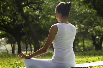Young woman sitting in lotus position in a park