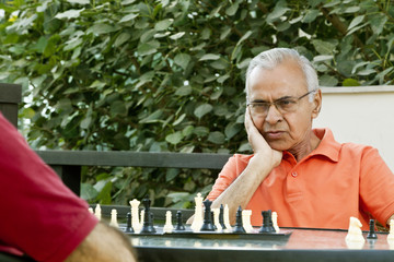 Senior man with hand on chin looking at chess board and thinking of his next move