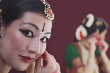 Close-up portrait of Bharatanatyam dancer getting dressed in front of mirror