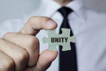 Businessman showing puzzle piece with Unity text.