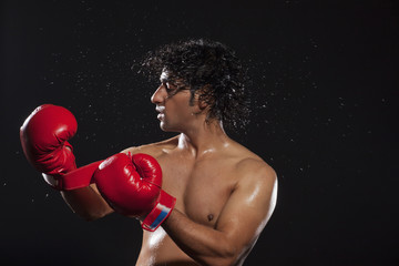 Young man tossing hair while wearing boxing gloves