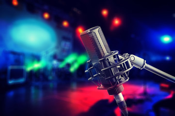 Professional studio microphone on stage during concert, blurred background