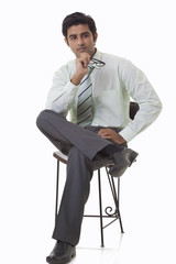Handsome young executive sitting on chair and looking away