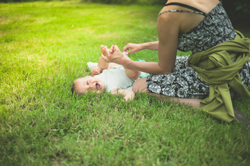 Mother changing diaper of baby in nature