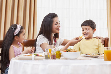 Cheerful mother feeding her son pizza with daughter sitting besides