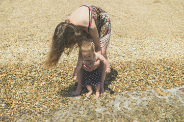 Young mother helping baby go paddle in the sea