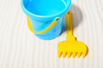 Bucket with rake on sand