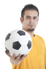 Portrait of young man holding soccer ball over white background