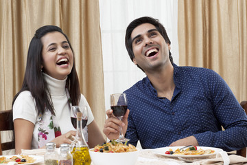 Cheerful young couple enjoying the meal at restaurant