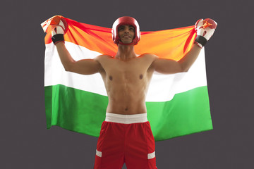 Happy Indian male boxer with national flag standing against gray background