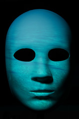 Textured mask with underwater painted surface, neutral expression on dark background.
