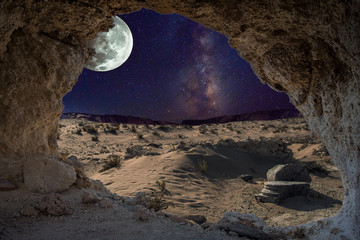 An unrealistic night landscape through a cave with milky, moon in eclipse, and desert with ruins of ancient columns.