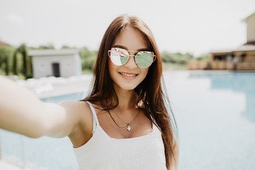 Portrait of beautiful girl taking a selfie at the swimming pool. Summer fun