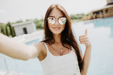 Portrait of beautiful girl taking a selfie at the swimming pool with thumbs up
