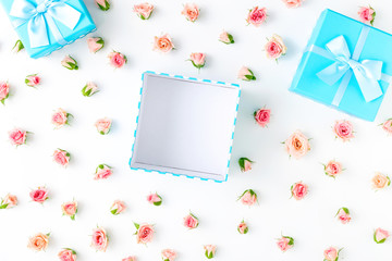 Open blue gift box with pink roses on white background