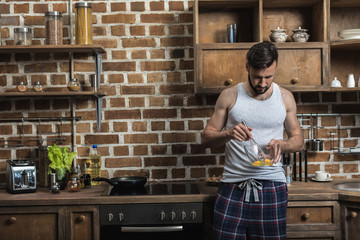 handsome bearded young man preparing eggs for breakfast in kitchen at home