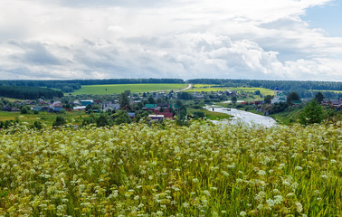 Beautiful summer rural landscape with river and clouds on blue sky. Russia. Ural. Village Sloboda