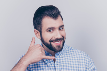 Cheerful brunet bearded freelancer is smiling, showing call sign, wearing casual smart, standing on a pure light background, sexy and playful
