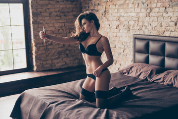Sexy naughty young brunette lady in seductive nice black silk underwear and stockings, on the brown sheets on bed, making selfie on her phone`s camera, for her lover, so hot and provocative!