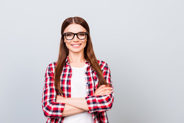 Successful and confident young brown haired lady, standing with crossed hands on pure backgrund and looking in the camera, She is in a casual checkered outfit, glasses, smiling