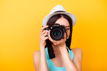 Close up of a photographer making a shot on a digital camera during vacation. She is wearing summer casual outfit and a hat, on bright yellow background