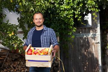 Glücklicher Bauer mit einer Kiste Äpfel - Außenaufnahme