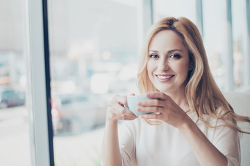 Good morning! Close up portrait of charming dreamy blond young lady drinking coffee. She is relaxed, in casual wear, in cafe, near the window