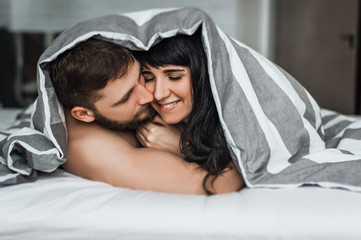 Man and woman hugging in bed. Loving couple in bed having sex. Couple in bed. Wedding night. Make love. Lovers in bed. The relationship between a man and a Woman. Sex between a man and a woman