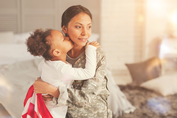 Adorable daughter giving her military mother a kiss
