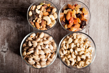 Healthy mix of dried nuts and sweets in was glass on wooden background in studio photo